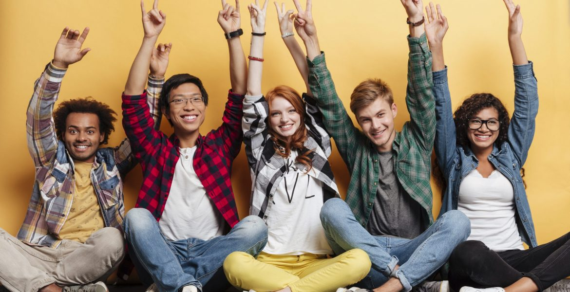 People celebrating success and showing peace sign with raised hands